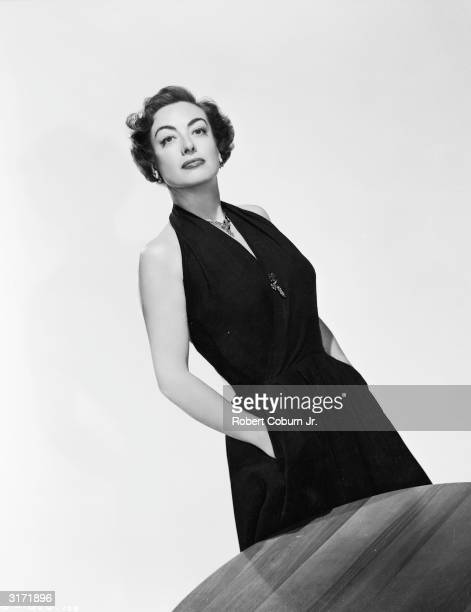 American film actress Joan Crawford standing by a table in a promotional picture for her latest film 'Harriet Craig'