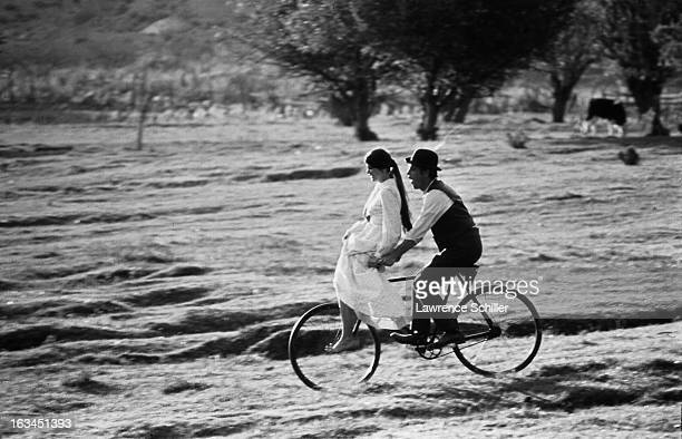 American film actress Katherine Ross balances on the handlebars of bicycle pedaled by actor Paul Newman in a scene from the film 'Butch Cassidy and...