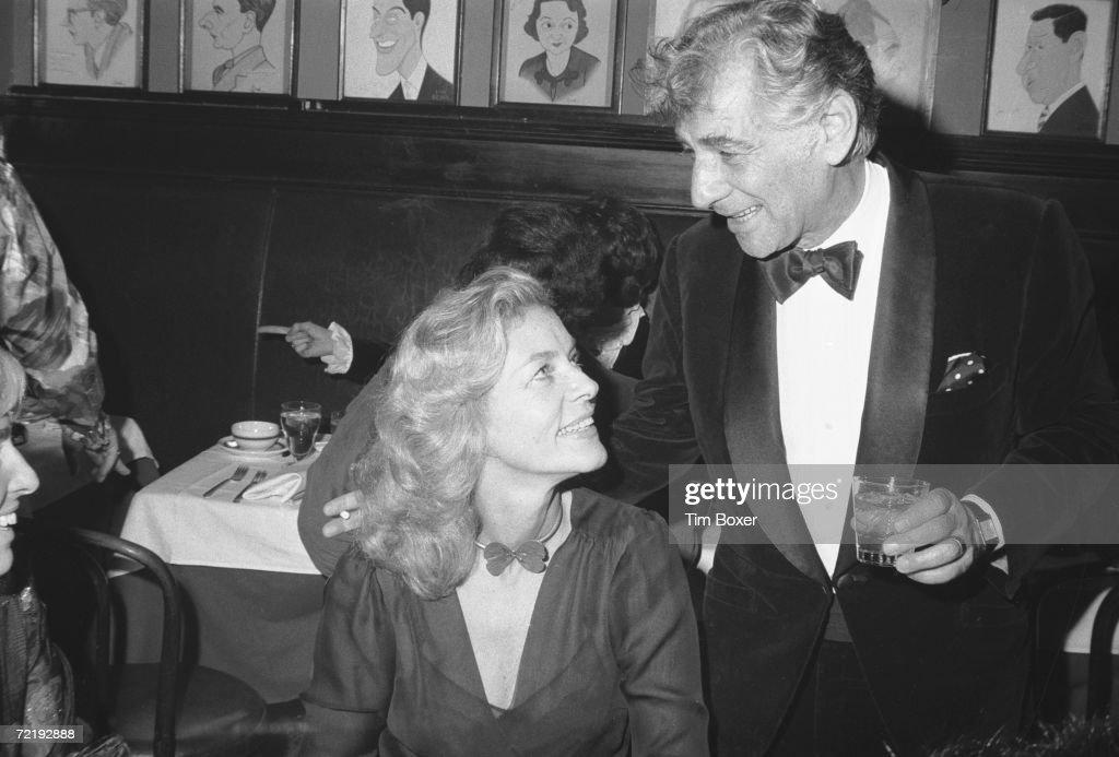 American film actress Lauren Bacall sits and listens as orchestra conductor Leonard Bernstein (1918 - 1990) talks at Sardi's restaurant, Manhattan, New York, 1971.