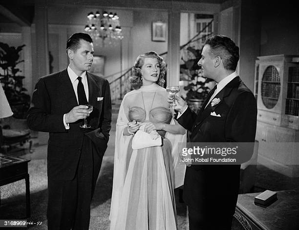 American film actress Rita Hayworth with Glenn Ford and Alexander Scourby in a scene from the action film 'Affair In Trinidad' directed by Vincent...