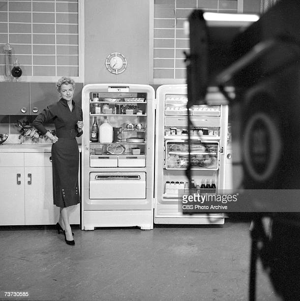American film actress, television host, and later consumer advocate Betty Furness stands beside an open Westinghouse refrigerator in a fake kitchen...
