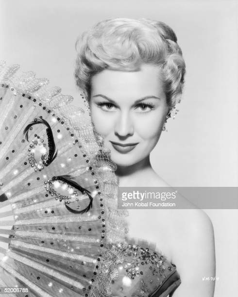 American film actress Virginia Mayo emerges from behind a large fan circa 1950