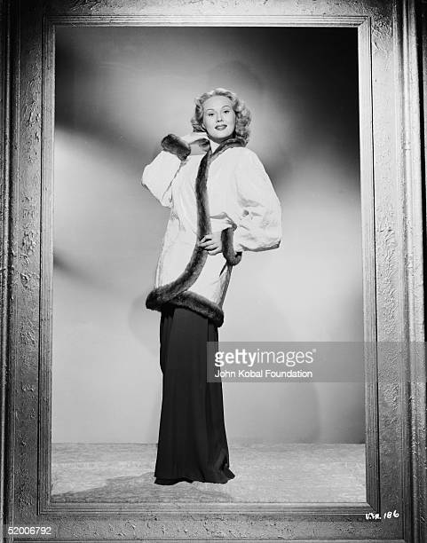 American film actress Virginia Mayo poses in a large picture frame wearing a furtrimmed jacket and loosefitting trousers circa 1950