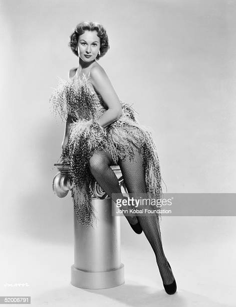 American film actress Virginia Mayo poses on a plinth dressed in a feathery dress and fishnet stockings circa 1950