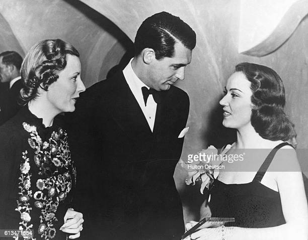American film actresses Fay Wray and Irene Dunne chatting to Cary Grant at a Hollywood party