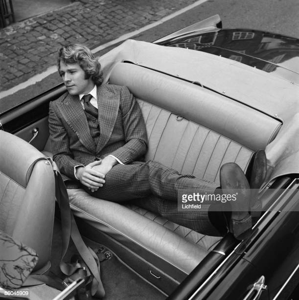 American film and television actor Ryan O'Neal photographed lying on the back seat of a convertible car on 12th March 1971