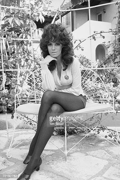 American film and television actress Lisa Todd poses for a photograph as she sits on a patio chair in short shorts and stockings with her legs...