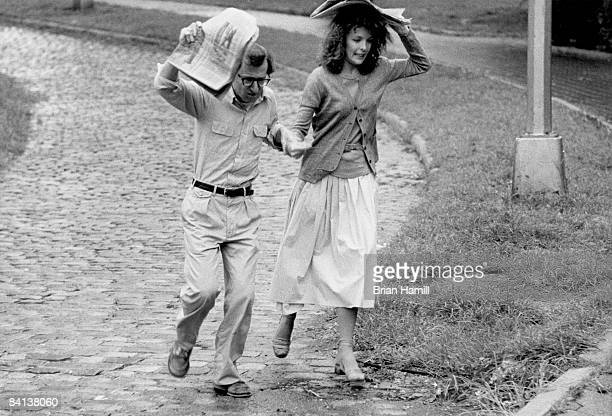 American film director actor and writer Woody Allen and actress Diane Keaton run through the rain with newspapers over their heads in a scene from...