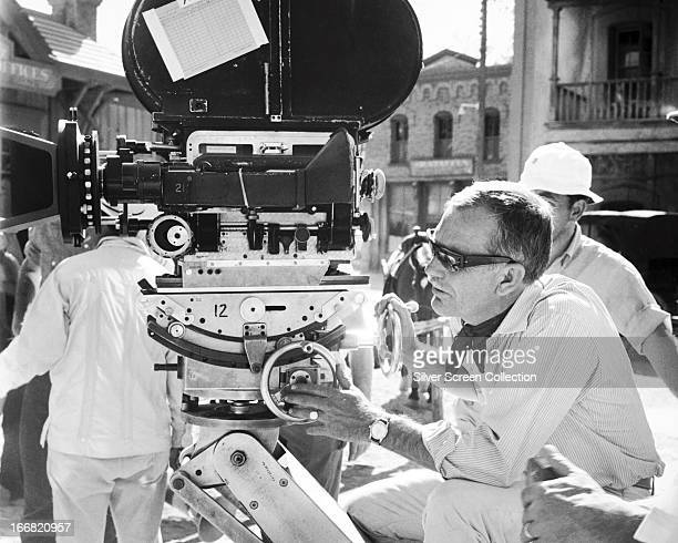 American film director and screenwriter Sam Peckinpah adjusting a movie camera on the set of 'The Wild Bunch' 1969