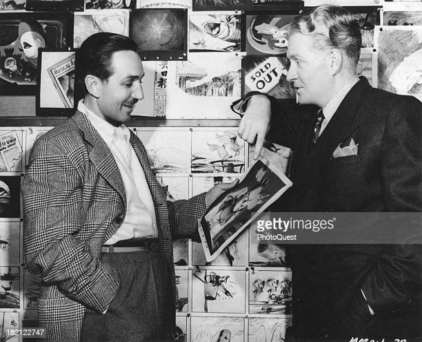 American film director animator and businessman Walt Disney and singer and actor Nelson Eddy discuss an illustration of 'Willie the Whale' in the...