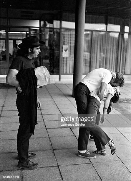 American film director Brian G Hutton watches as actor Clint Eastwood dips an unidentified woman as he kisses her during filming their 'Kelly's...