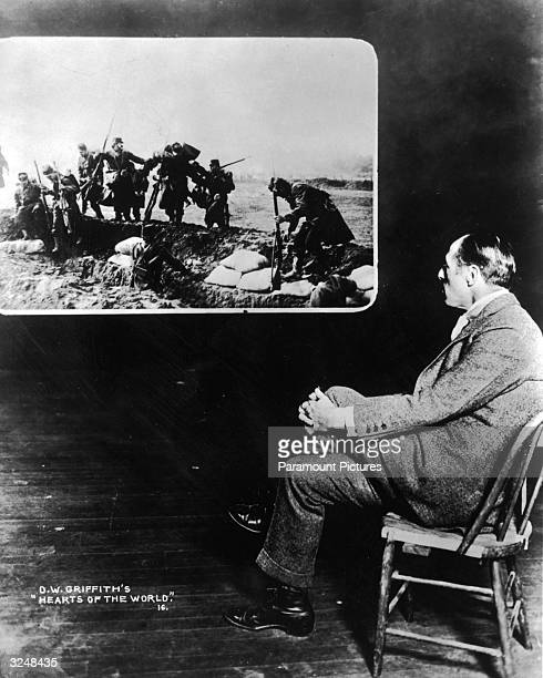 American film director D W Griffith watches footage from his film 'Hearts of The World' in which World War I soldiers fight along a trench