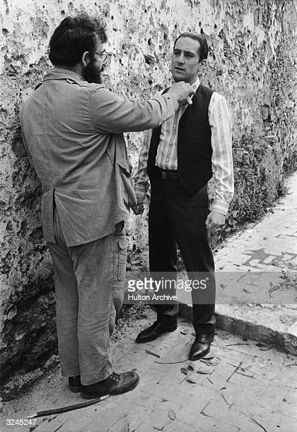 American film director Francis Ford Coppola stands in an alley and holds a knife to American actor Robert De Niro's throat while directing him on...