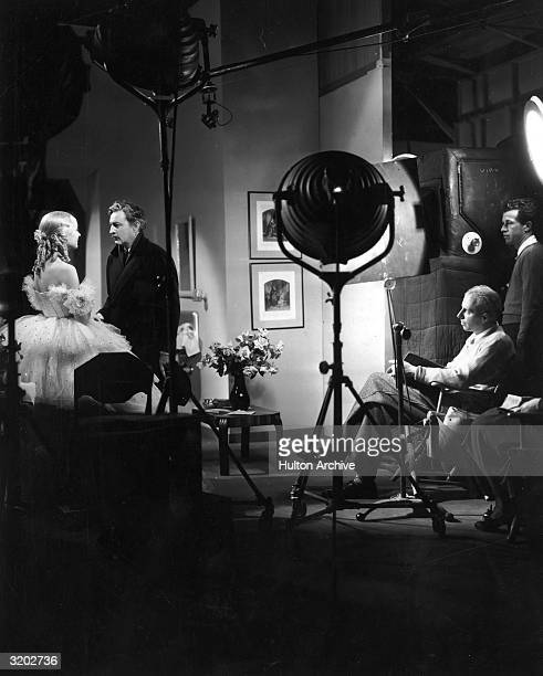 American film director Howard Hawks sits in a folding chair and watches American actors Carole Lombard and John Barrymore perform a scene on the set...
