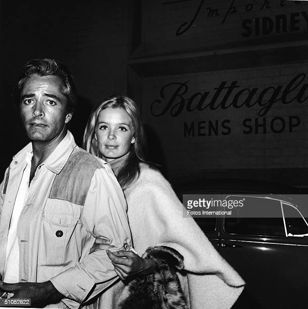 American film director John Derek and his wife, actor Linda Evans, look at the camera while standing outside a men's clothing shop, July 1967.