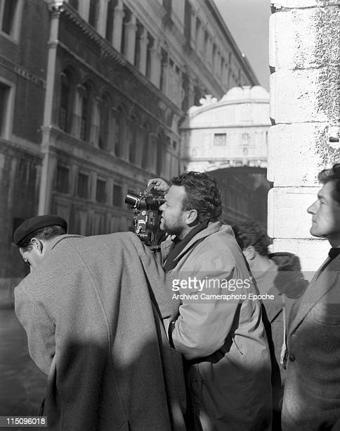 American film director Orson Welles shooting with a cinecamera on the set of the movie Othello filming next to the Ponte dei Sospiri members of the...
