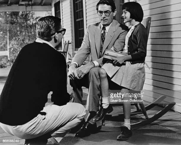 American film director Robert Mulligan talks with actors Gregory Peck and Mary Badham on the set of 'To Kill a Mockingbird' , 1962.