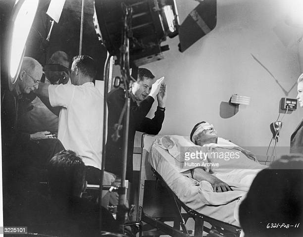 American film director Roger Corman lines up a shot as Welshborn actor Ray Milland lays in a hospital bed with a bandage over his eyes on the set of...