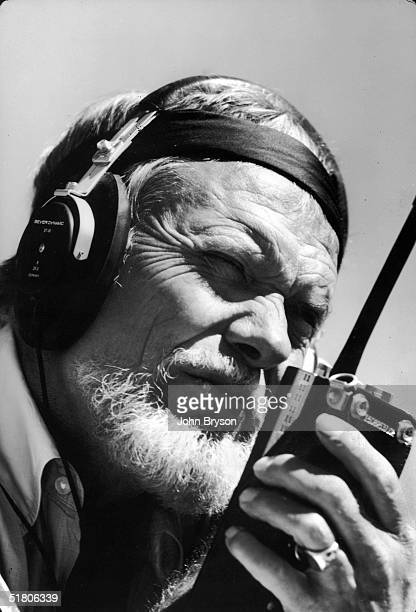 American film director Sam Peckinpah holds a CB radio while directing a scene from the film 'Convoy' New Mexico 1977