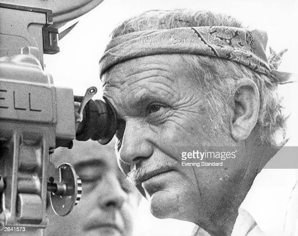 American film director Sam Peckinpah looking through the camera lens whilst filming 'Cross of Iron'