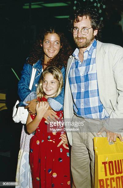 American film director Steven Spielberg out shopping with his wife Amy Irving and child actress Drew Barrymore, circa 1985. Barrymore starred in...