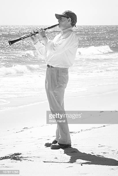 American film director Woody Allen plays his clarinet on an unspecified beach early 2000s