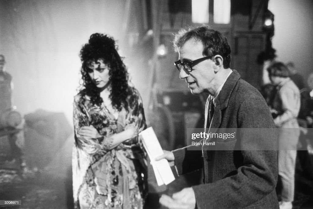 American film director, writer, and actor Woody Allen directs a scene as American singer and actor Madonna stands in the background on the set of Allen's film, 'Shadows and Fog,' in which they both starred.