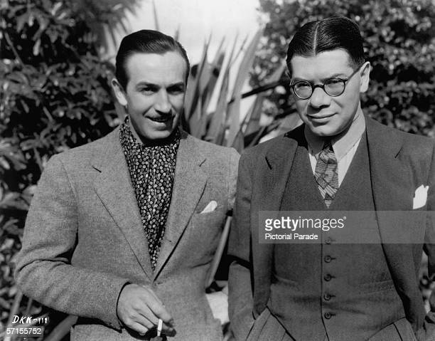 American film producer and animator Walt Disney smokes a cigarette and stands with advertising executive and salesman Kay Kamen dressed in a three...