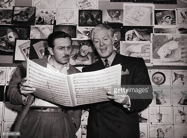 American film producer and creator of Disney World Walt Disney holds sheet music with actor Eddy Nelson