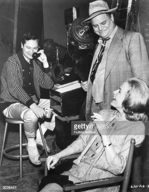 American film producer and director Roger Corman sits and talks on the telephone as actor Diana Van der Vlis and comedian Don Rickles chat on the set...