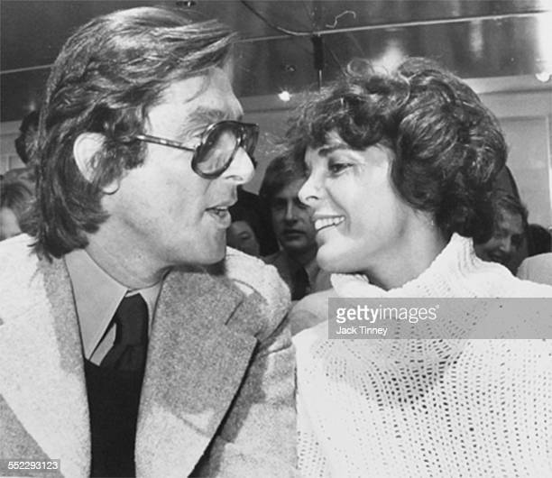 American film producer and executive Robert Evans talks with actress Ali MacGraw at an unidentified Fashion Week event, New York, New York, 1969.