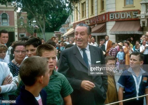 American film producer and studio executive Walt Disney stands with a group of boys and others as they wait for a parade on Main Street USA at...
