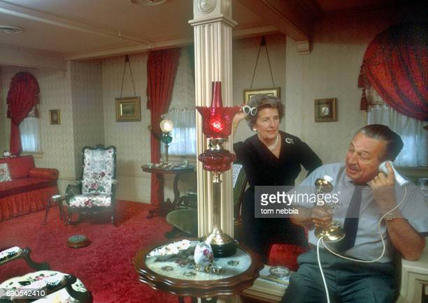 American film producer and studio executive Walt Disney talks on the telephone as his wife Lillian Disney watches Anaheim California January 1962 The...