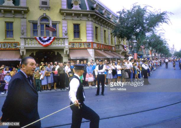 American film producer and studio executive Walt Disney walks on Main Street USA during a parade at Disneyland Anaheim California August 1962