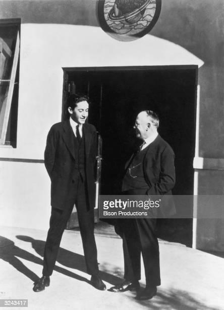 American film producer Irving Thalberg left and Germanborn film executive Carl Laemmle talk on the lot of Universal Studios California