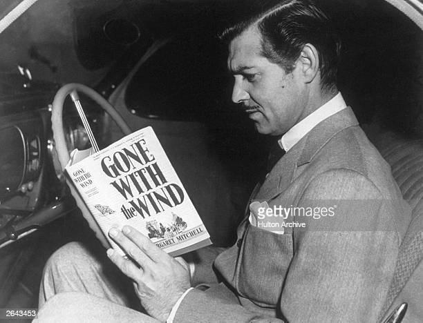 American film star Clark Gable reading the novel 'Gone With the Wind' by Margaret Mitchell His greatest role was that of Rhett Butler in the MGM film...