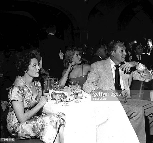 1954 American film star Forrest Tucker watches a cabaret at the Pigalle with Diane Hart and Jill Adams