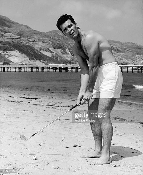 American film star James Garner practises his golf stroke on the beach in Malibu, circa 1960.