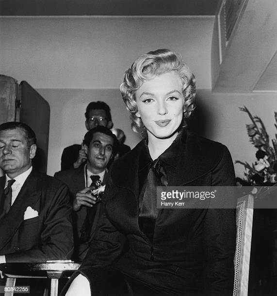 American film star Marilyn Monroe at a press conference at the Savoy Hotel, London, 17th July 1956. On the left is her co-star in the film 'The...