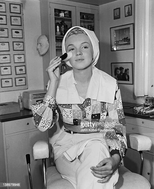 American film star Marilyn Monroe begins the process of applying her makeup 1948