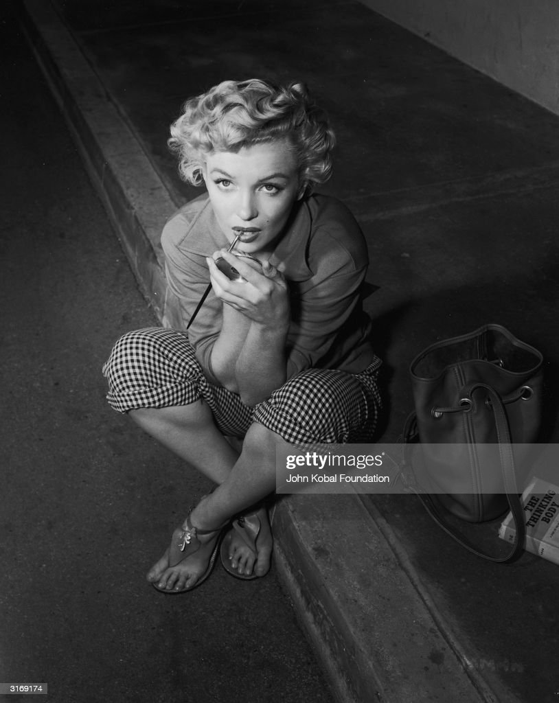 American film star Marilyn Monroe (1926 - 1962), born Norma Jean Mortensen in Los Angeles, sits on the kerb to apply her make-up. The book beside her is 'The Thinking Body' by Todd.