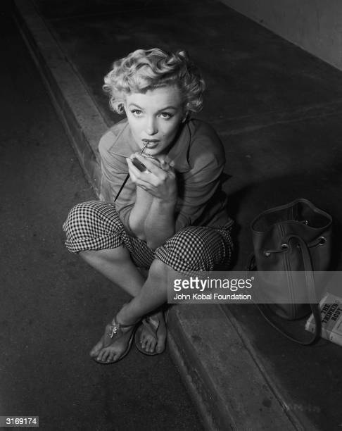 American film star Marilyn Monroe born Norma Jean Mortensen in Los Angeles sits on the kerb to apply her makeup The book beside her is 'The Thinking...