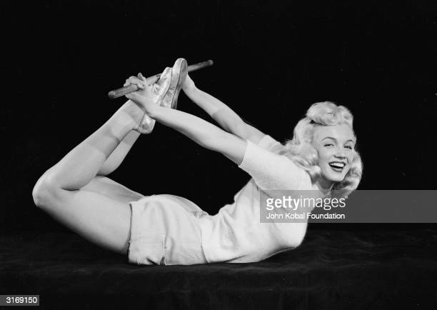 American film star Marilyn Monroe curls herself into a bow shape and assumes a yogic exercise position