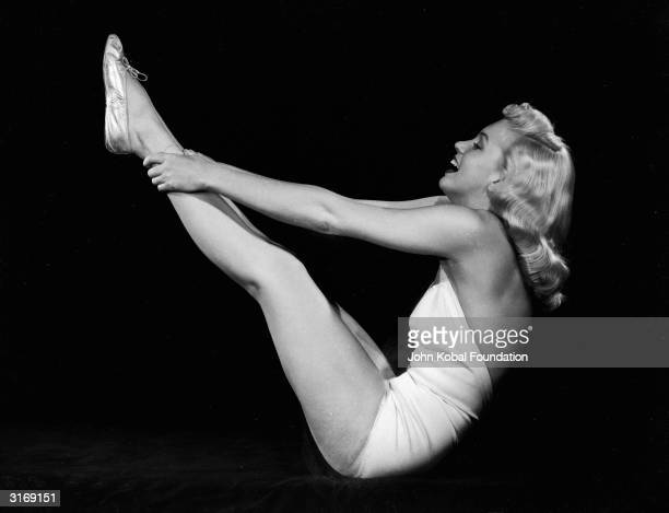 American film star Marilyn Monroe raises her legs in the air and assumes a yogic exercise position
