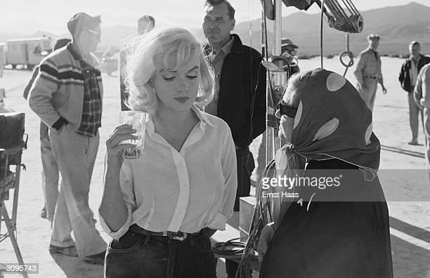 American film star Marilyn Monroe with her acting coach Paula Strasberg the wife of 'method' teacher Lee Strasberg on the set of 'The Misfits' being...
