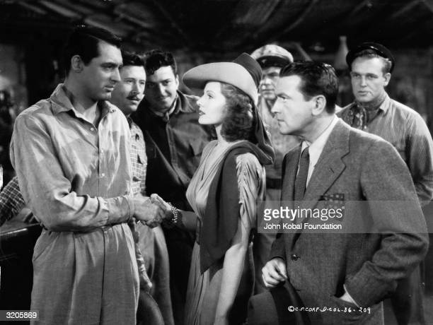 American film stars Cary Grant Rita Hayworth and Richard Barthelmess together during the making of 'Only Angels Have Wings' which was directed by...