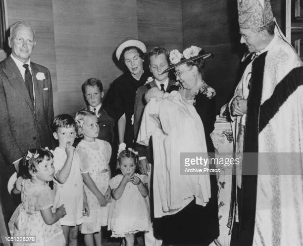 American filmmaker John Farrow with his wife, actress Maureen O'Sullivan and their children at the baptism of baby Teresa Farrow, USA, 1951. Holding...
