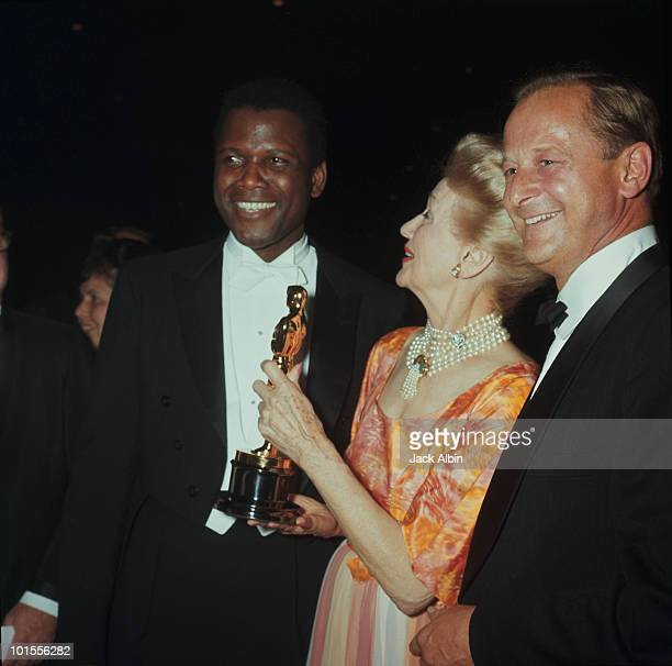 American filmmaker Ralph Nelson and gossip columnist Hedda Hopper congratulate actor Sidney Poitier on winning his Academy Award at the Beverly...