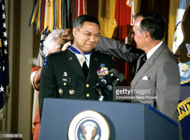 American First Lady Barbara Bush fastens the Presidential Medal of Freedom around the neck of Chairman of the Joint Chiefs of Staff US Army General...