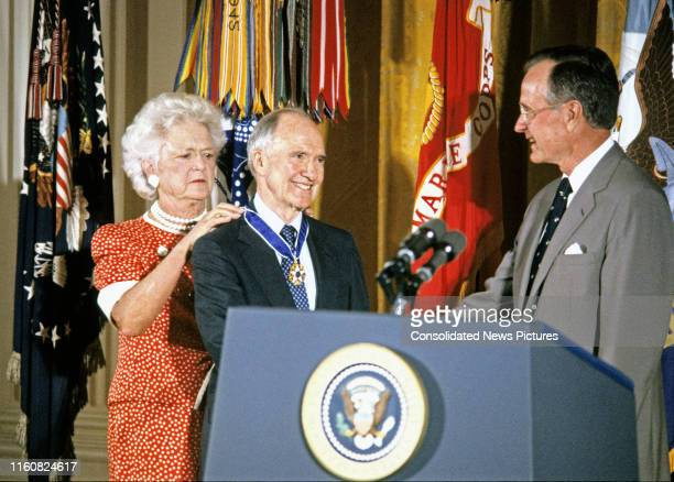 American First Lady Barbara Bush fastens the Presidential Medal of Freedom around the neck of National Security Advisor Brent Scowcroft as he shakes...